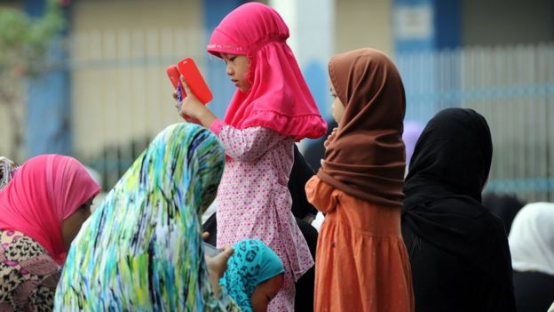 A Muslim girl is on the phone while her family sit around her