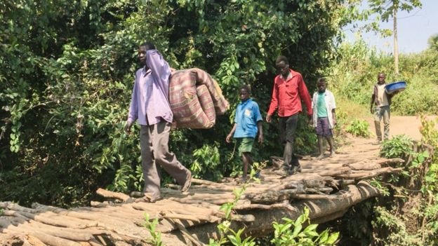 Refugees cross a rudimentary bridge as they make their way into Uganda