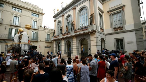 People stand and watch in front of Theater-Museum Dali during the exhumation of Spanish artist Salvador Dali