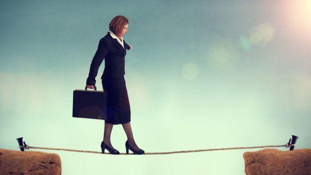 Mujer trajeada camina sobre una cuerda entre dos picos.
