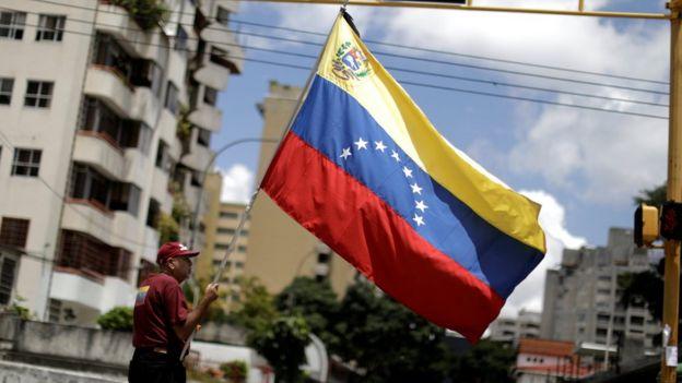 Hombre sosteniendo la bandera de Venezuela en Caracas.