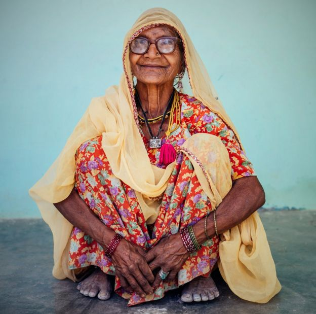 Indian old woman sitting on a squat.
