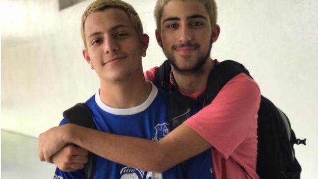 Dois adolescentes se abraçam e sorriram amplamente