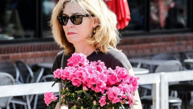 A fan carries flowers as she pays her respects to the late rock