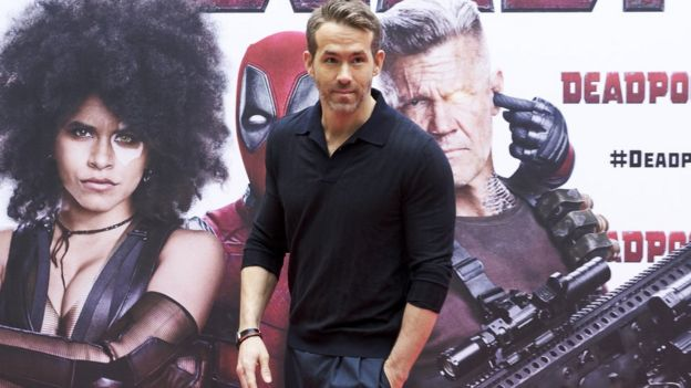 Ryan Reynolds in fron of a Deadpool poster