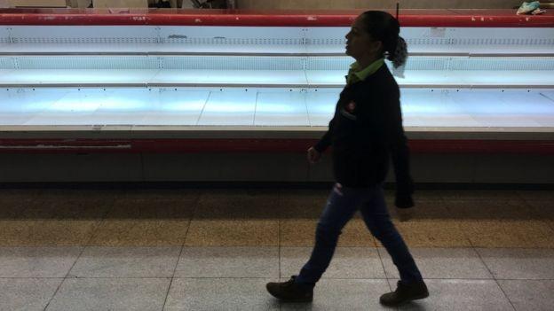 Una mujer pasea frente a una cámara vacía.