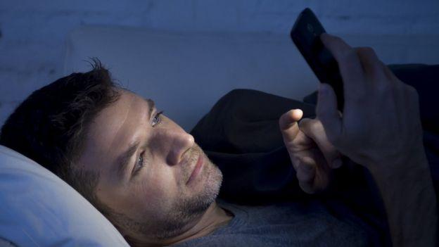 Homem usando celular à noite