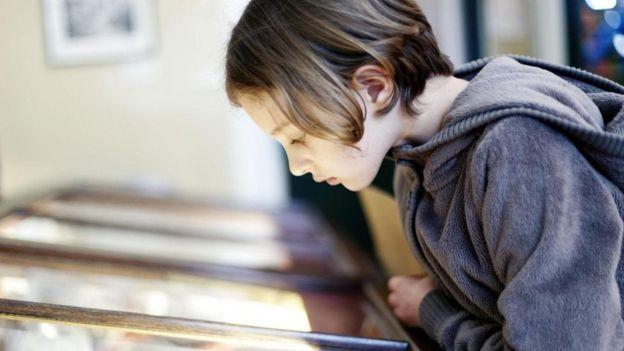 فتى يدقق النظر في معروضات أحد المتاحف
