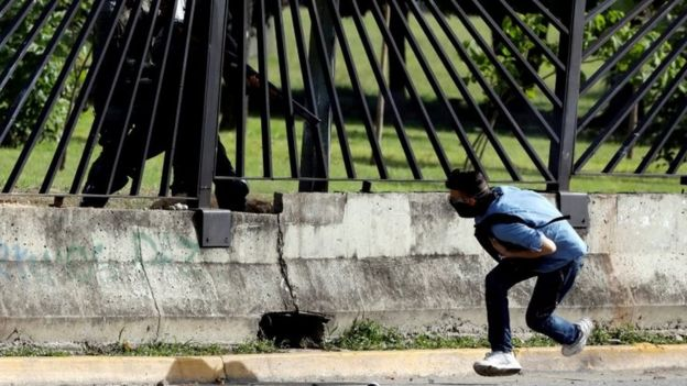 A member of the riot security forces points a gun through the fence of an air force base at David Jose Vallenilla, who was fatally injured during clashes at a rally against Venezuelan President Nicolas Mauro's government in Caracas, Venezuela, June 22, 2017.