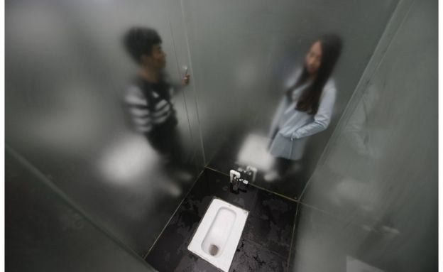 A squat toilet cubicle surrounded by lightly frosted glass  with a man  on the other. Glass loos with a view open in China   BBC News