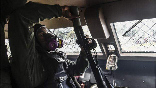 Una guardia nacional carga su arma con una bomba lacrimógena.