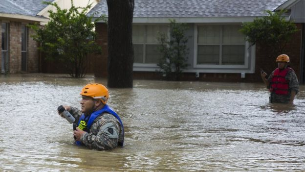 Un rescatista camina por la parte oeste de Houston buscando a personas que puedan estar varadas en sus casas.