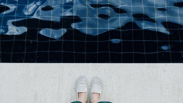 Pessoa na beira de uma piscina