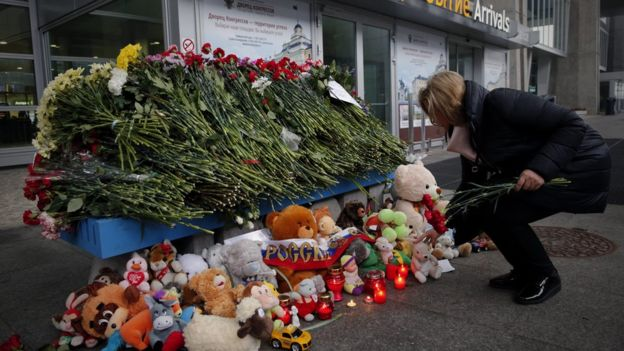 Well-wisher leaves flowers at a tribute to the crash victims at St Petersburg's Pulkovo airport - 1 November