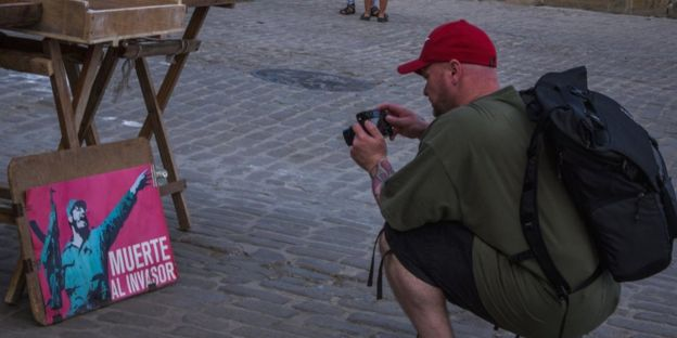 A tourist takes a picture of a painting in Havana