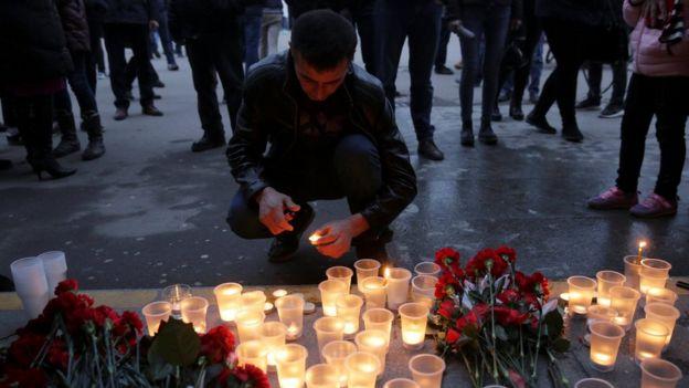 Un hombre enciende una vela en memoria de las víctimas de la explosión en el metro
