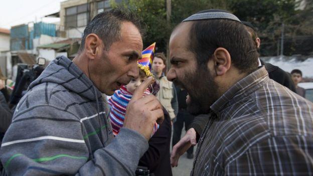 Еврейский поселенец спорит с палестинцем.