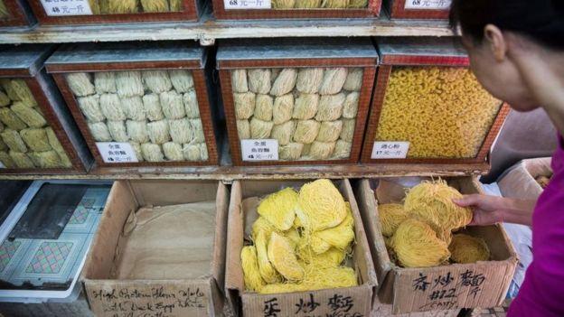 Mujer comprando noodles en un mercado de Hong Kong