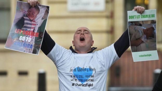 Hombre protestando frente a los tribunales con carteles que dicen: