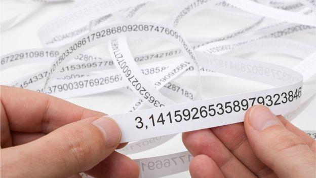 Manos sosteniendo papel con dígitos interminables de Pi.