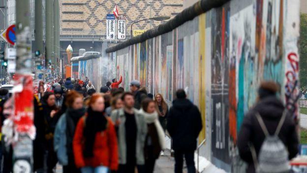 Turistas caminham nas proximidades do que restou do Muro de Berlim