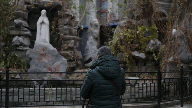 Una mujer ora ante una imagen de la virgen María en China