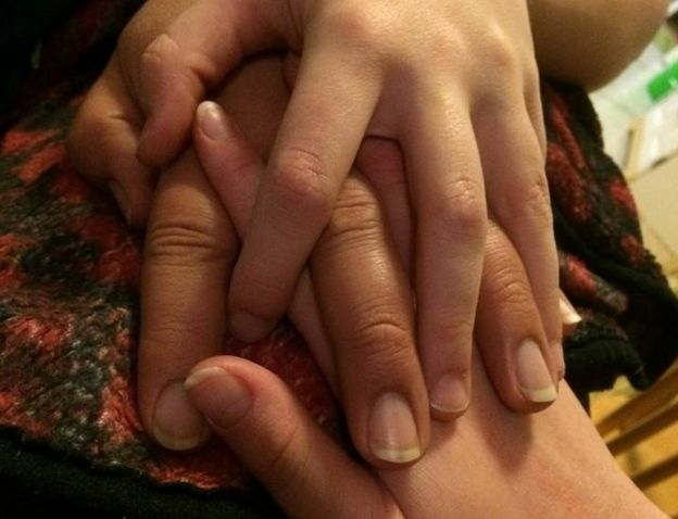 Three intertwined hands