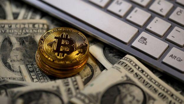 Billetes de dólar estadounidense bajo monedas de bitcoin