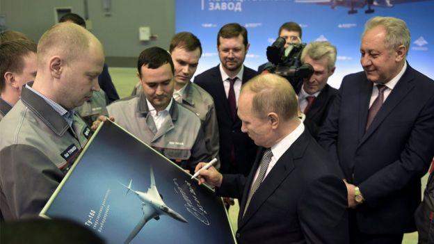 El presidente ruso, Vladimir Putin, firma una fotografía del bombardero nuclear TU-160M.