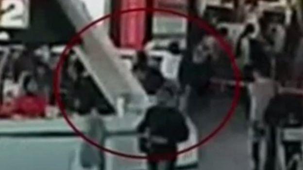 El momento en que una de las mujeres le pasa un pañuelo por la cara a Kim Jong-nam.