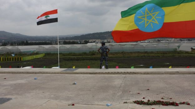 A federal policeman stands guard between the Oromo regional flag (left) and Ethiopia's national flag at the October ceremony marking the opening of the Addis Ababa-Djibouti railway