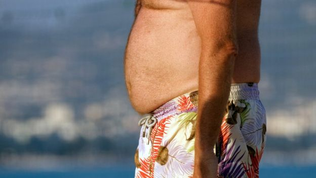 Belly fat whats the best way to get rid of it bbc news mans midriff in beach shorts on beach ccuart Images