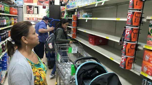 Varias personas buscan víveres en un supermercado con estantes vacíos en Miami, Florida.