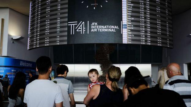 People walk through international arrivals at terminal four at John F Kennedy (JFK) airport