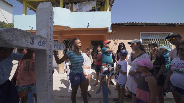 Una joven enseñando una cruz a unos visitantes.