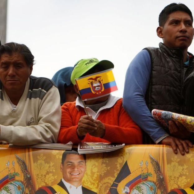 Hombres con bandera de Ecuador e imágenes de Correa.