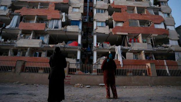 Dos personas frente a un edificio dañado