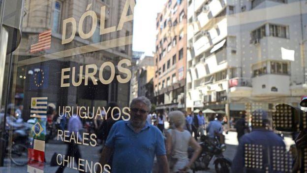 un hombre mira una vitrina con información sobre cambio de moneda