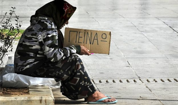 """A woman holds a cardboard reading in Greek """"I"""" m hungry"""" on 17 March 2011 in central Athens"""