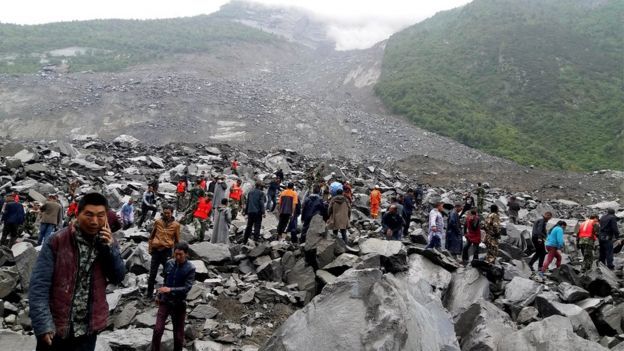 People search for survivors following a landslide in Xinmo Village in Maoxian county, 24 June 2017