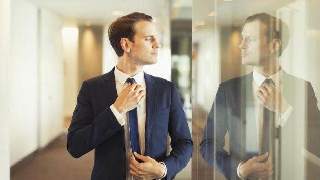 Una persona ajustándose la corbata viéndose en un panel de vidrio de una oficina