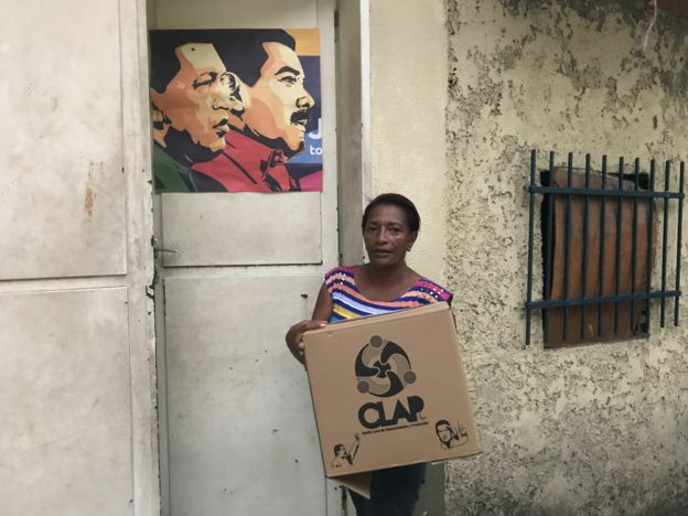 Una mujer con una caja CLAP