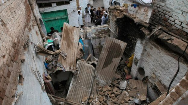 earthquake leaves hundreds dead news people stand outside a house damaged by an earthquake in peshawar 26 oct