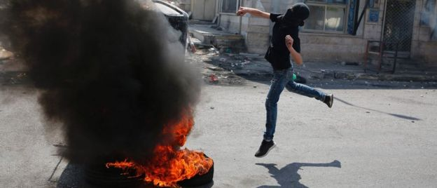 A masked Palestinian protester throws a stone at Israeli troops at the Qalandia checkpoint, 22 May