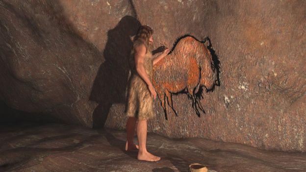 Hombre de la edad de piedra dibujando una pintura rupestre