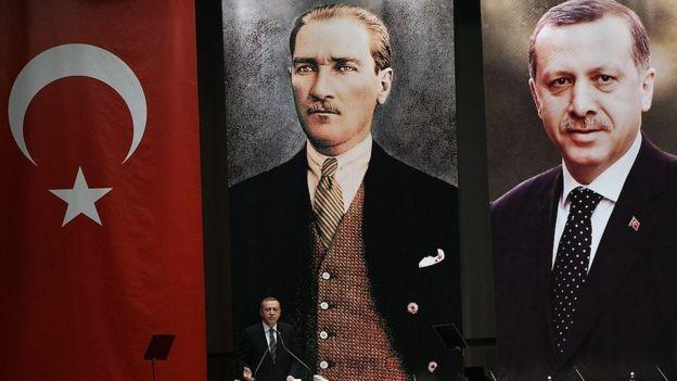 Erdogan habla frente a posters con su imagen y la de Ataturk.