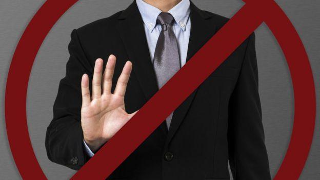 Homem engravatado com faixa de proibido