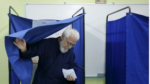 A Greek Orthodox priest exits a voting booth holding his ballot at a station in Athens on 20 September 2015