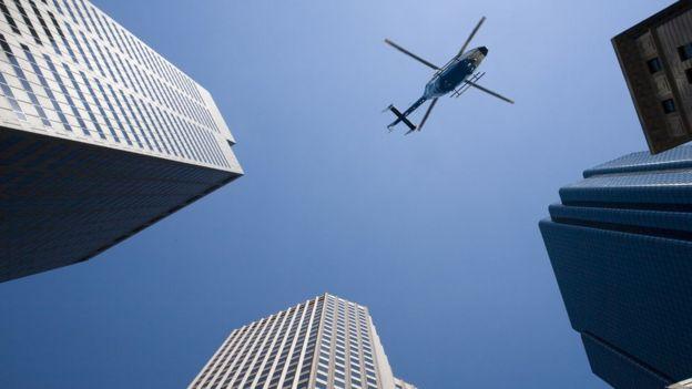 Vista al cielo de rascacielos y un helicóptero.