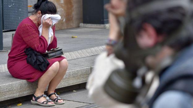 Una mujer que sufre los efectos del gas lacrimógeno se tapa la cara con un trapo blanco, mientras está sentada en una vereda.